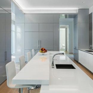 Diseño de cocina moderna con fregadero de doble seno, armarios con paneles lisos, puertas de armario blancas, salpicadero verde, salpicadero de vidrio templado, suelo de madera clara y una isla