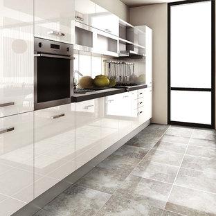 アトランタの中サイズのモダンスタイルのおしゃれなキッチン (ドロップインシンク、フラットパネル扉のキャビネット、白いキャビネット、人工大理石カウンター、メタリックのキッチンパネル、メタルタイルのキッチンパネル、シルバーの調理設備の、トラバーチンの床、アイランドなし、マルチカラーの床) の写真