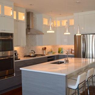 Modern inredning av ett stort kök, med en undermonterad diskho, släta luckor, grå skåp, bänkskiva i kvartsit, grått stänkskydd, stänkskydd i stenkakel, rostfria vitvaror, mellanmörkt trägolv och en köksö