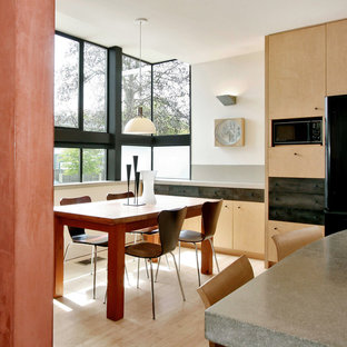 Esempio di una cucina abitabile minimalista con ante lisce, ante in legno chiaro e top in cemento