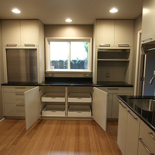 Small modern l-shaped kitchen pantry in Sacramento with an undermount sink, flat-panel cabinets, beige cabinets, granite benchtops, beige splashback, glass tile splashback, stainless steel appliances, bamboo floors and no island.