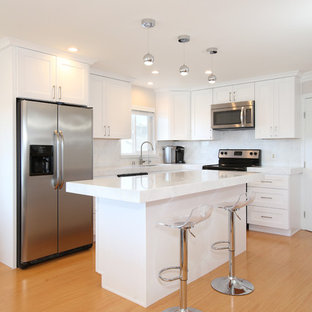 Inspiration for a small modern u-shaped eat-in kitchen in Los Angeles with a drop-in sink, flat-panel cabinets, white cabinets, quartzite benchtops, white splashback, stainless steel appliances, light hardwood floors and with island.