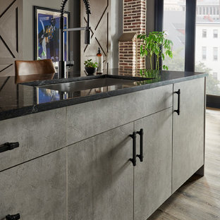 Mid-sized modern eat-in kitchen inspiration - Example of a mid-sized minimalist single-wall brown floor eat-in kitchen design in New York with an undermount sink, flat-panel cabinets, black cabinets, solid surface countertops, gray backsplash, glass sheet backsplash, stainless steel appliances, an island and black countertops