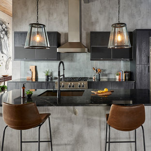 Mid-sized modern eat-in kitchen photos - Inspiration for a mid-sized modern single-wall brown floor eat-in kitchen remodel in New York with an undermount sink, flat-panel cabinets, black cabinets, solid surface countertops, gray backsplash, glass sheet backsplash, stainless steel appliances, an island and black countertops