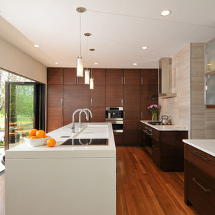 Photo of a mid-sized contemporary l-shaped open plan kitchen in Chicago with flat-panel cabinets, dark wood cabinets, beige splashback, with island, an integrated sink, quartz benchtops, panelled appliances, light hardwood floors and stone tile splashback.