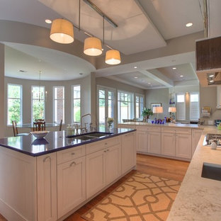 Large modern u-shaped eat-in kitchen in Houston with a double-bowl sink, shaker cabinets, quartz benchtops, multi-coloured splashback, white cabinets, panelled appliances, with island, medium hardwood floors, brown floor and purple benchtop.