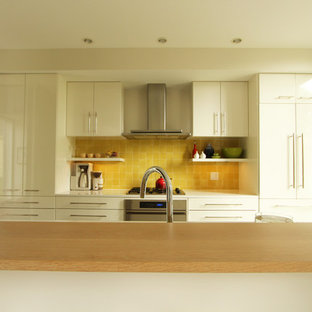 Photo of a small modern single-wall open plan kitchen in Other with a double-bowl sink, flat-panel cabinets, white cabinets, quartz benchtops, yellow splashback, ceramic splashback, panelled appliances, concrete floors and with island.