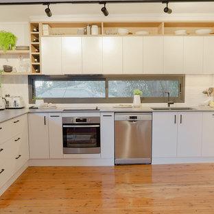 Modelo de cocina comedor en L, minimalista, de tamaño medio, con fregadero bajoencimera, armarios con paneles lisos, puertas de armario blancas, encimera de cuarzo compacto, salpicadero verde, salpicadero de vidrio, electrodomésticos de acero inoxidable, suelo de madera clara, suelo naranja y encimeras grises