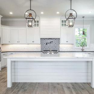 Foto på ett mellanstort funkis vit u-kök, med en undermonterad diskho, luckor med infälld panel, vita skåp, marmorbänkskiva, vitt stänkskydd, stänkskydd i tunnelbanekakel, rostfria vitvaror, ljust trägolv, en köksö och grått golv