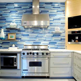 オースティンのコンテンポラリースタイルのおしゃれなキッチン (再生ガラスカウンター、フラットパネル扉のキャビネット、グレーのキャビネット、青いキッチンパネル、ガラスタイルのキッチンパネル、シルバーの調理設備) の写真