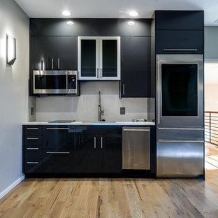 Ispirazione per una piccola cucina lineare minimal chiusa con lavello sottopiano, ante lisce, ante nere, elettrodomestici in acciaio inossidabile e nessuna isola