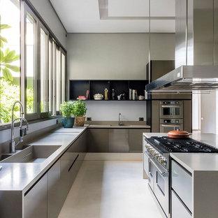 サンフランシスコの広いコンテンポラリースタイルのおしゃれなキッチン (ドロップインシンク、フラットパネル扉のキャビネット、グレーのキャビネット、クオーツストーンカウンター、白いキッチンパネル、石スラブのキッチンパネル、シルバーの調理設備、コンクリートの床、白い床、グレーのキッチンカウンター) の写真