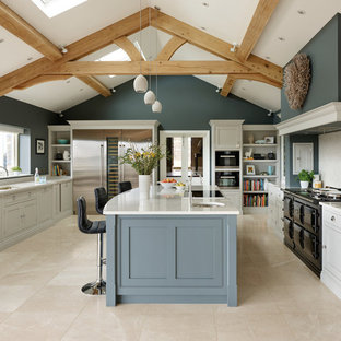 This is an example of an expansive rural galley open plan kitchen in Manchester with engineered stone countertops, an island, a submerged sink, recessed-panel cabinets, stainless steel appliances and white worktops.