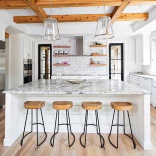Foto på ett maritimt flerfärgad kök, med en rustik diskho, skåp i shakerstil, vita skåp, flerfärgad stänkskydd, ljust trägolv, en köksö, beiget golv, granitbänkskiva och stänkskydd i marmor