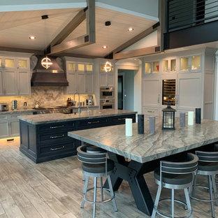 Geräumige Moderne Küche mit Unterbauwaschbecken, Küchengeräten aus Edelstahl, Sperrholzboden, zwei Kücheninseln, grauem Boden und grauer Arbeitsplatte in Chicago
