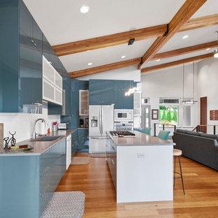 カンザスシティの大きいコンテンポラリースタイルのおしゃれなキッチン (アンダーカウンターシンク、フラットパネル扉のキャビネット、ターコイズのキャビネット、クオーツストーンカウンター、白いキッチンパネル、磁器タイルのキッチンパネル、白い調理設備、淡色無垢フローリング、茶色い床、グレーのキッチンカウンター) の写真