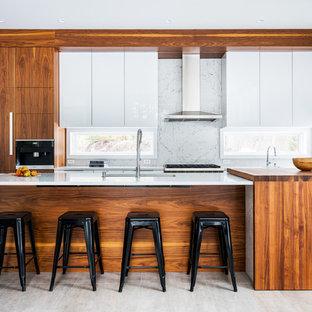バーリントンの中サイズのモダンスタイルのおしゃれなアイランドキッチン (フラットパネル扉のキャビネット、大理石カウンター、白いキッチンパネル、大理石の床、セラミックタイルの床、ベージュの床、アンダーカウンターシンク、白いキャビネット、パネルと同色の調理設備、白いキッチンカウンター) の写真