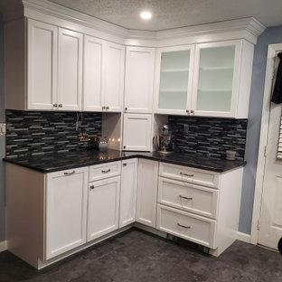Mittelgroße Moderne Wohnküche ohne Insel in L-Form mit Waschbecken, flächenbündigen Schrankfronten, weißen Schränken, Granit-Arbeitsplatte, bunter Rückwand, Glasrückwand, Küchengeräten aus Edelstahl, Vinylboden, grauem Boden und grauer Arbeitsplatte in Boston