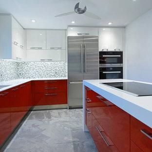 Foto de cocina en L, minimalista, grande, abierta, con fregadero bajoencimera, armarios con paneles lisos, puertas de armario blancas, encimera de cuarcita, salpicadero verde, electrodomésticos de acero inoxidable y una isla