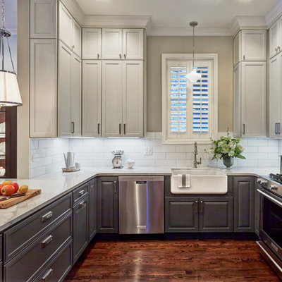 Example of a mid-sized farmhouse u-shaped dark wood floor open concept kitchen design in Other with a farmhouse sink, recessed-panel cabinets, gray cabinets, quartz countertops, white backsplash, subway tile backsplash, stainless steel appliances and a peninsula