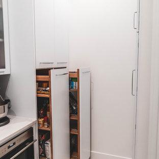 他の地域の小さいモダンスタイルのおしゃれなキッチン (アンダーカウンターシンク、フラットパネル扉のキャビネット、白いキャビネット、クオーツストーンカウンター、白いキッチンパネル、シルバーの調理設備、セラミックタイルの床、白い床、白いキッチンカウンター) の写真