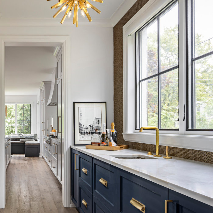 The custom Butler's Panty showcases high gloss navy cabinetry, which conceals both a Scotsman Ice Maker and Sub Zero Refrigerator Drawers. The custom mosaic backsplash is created from gold harlequin i