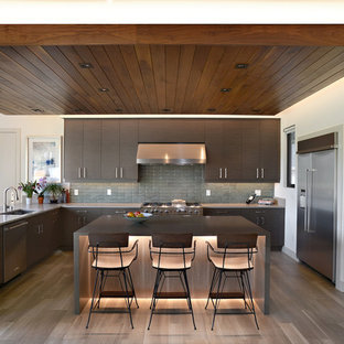 Cette photo montre une cuisine américaine moderne en U de taille moyenne avec un évier encastré, un placard à porte plane, des portes de placard marrons, un plan de travail en quartz modifié, une crédence verte, une crédence en carreau de céramique, un électroménager en acier inoxydable, un sol en bois brun, un îlot central, un sol marron et un plan de travail gris.