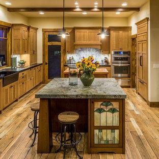 他の地域の広いラスティックスタイルのおしゃれなキッチン (エプロンフロントシンク、シェーカースタイル扉のキャビネット、中間色木目調キャビネット、ソープストーンカウンター、マルチカラーのキッチンパネル、石スラブのキッチンパネル、パネルと同色の調理設備、無垢フローリング、茶色い床、黒いキッチンカウンター) の写真