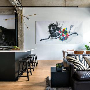 Offene Industrial Küche mit flächenbündigen Schrankfronten, schwarzen Schränken, Küchenrückwand in Schwarz, braunem Holzboden, Kücheninsel und weißer Arbeitsplatte in Washington, D.C.