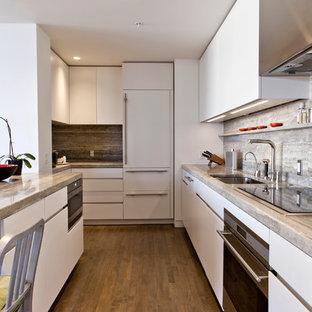 ミネアポリスのモダンスタイルのおしゃれなキッチン (アンダーカウンターシンク、フラットパネル扉のキャビネット、白いキャビネット、グレーのキッチンパネル、パネルと同色の調理設備、トラバーチンの床) の写真