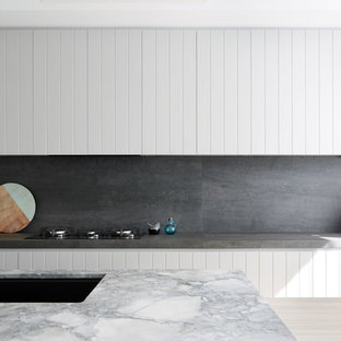 Contemporary galley kitchen in Sydney with an undermount sink, white cabinets, grey splashback, stone slab splashback, with island and grey benchtop.