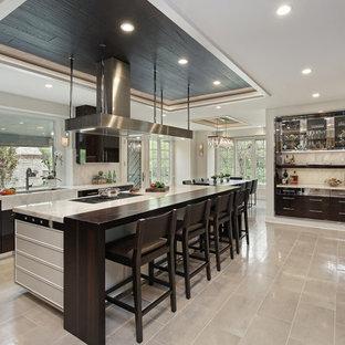 Inspiration för mycket stora moderna vitt kök, med en trippel diskho, släta luckor, skåp i mörkt trä, bänkskiva i kvartsit, vitt stänkskydd, stänkskydd i sten, rostfria vitvaror, en köksö, klinkergolv i porslin och beiget golv