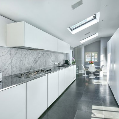Eat-in kitchen - modern gray floor eat-in kitchen idea in London with an integrated sink, flat-panel cabinets, white cabinets, stainless steel countertops, white backsplash, marble backsplash and no island