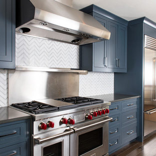 This is an example of a mid-sized transitional kitchen in Other with an undermount sink, recessed-panel cabinets, blue cabinets, zinc benchtops, white splashback, ceramic splashback, stainless steel appliances, medium hardwood floors, a peninsula and brown floor.