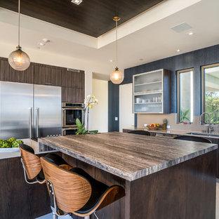 ロサンゼルスの大きいビーチスタイルのおしゃれなキッチン (アンダーカウンターシンク、フラットパネル扉のキャビネット、中間色木目調キャビネット、人工大理石カウンター、ベージュキッチンパネル、シルバーの調理設備の、トラバーチンの床、ベージュのキッチンカウンター) の写真