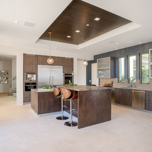 Large contemporary eat-in kitchen appliance - Inspiration for a large contemporary l-shaped limestone floor and white floor eat-in kitchen remodel in Los Angeles with a drop-in sink, flat-panel cabinets, dark wood cabinets, marble countertops, beige backsplash, stainless steel appliances, two islands and multicolored countertops