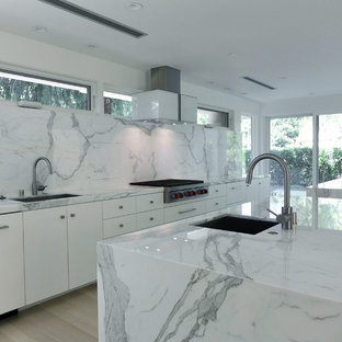 Photo of a large modern single-wall eat-in kitchen in Other with an undermount sink, flat-panel cabinets, white cabinets, marble benchtops, white splashback, stone slab splashback, stainless steel appliances, light hardwood floors and multiple islands.