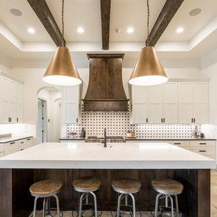 Mediterranean kitchen appliance - Kitchen - mediterranean u-shaped beige floor kitchen idea in Austin with a farmhouse sink, shaker cabinets, white cabinets, multicolored backsplash, stainless steel appliances, an island and black countertops