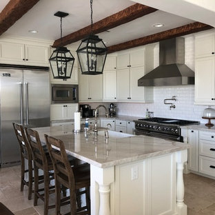 This is an example of a large mediterranean l-shaped open plan kitchen in Las Vegas with a farmhouse sink, shaker cabinets, white cabinets, quartzite benchtops, white splashback, ceramic splashback, stainless steel appliances, marble floors, with island, beige floor and multi-coloured benchtop.