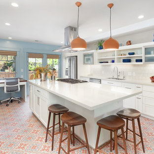 This is an example of a contemporary galley kitchen in San Francisco with an undermount sink, shaker cabinets, white cabinets, quartzite benchtops, white splashback, stainless steel appliances, porcelain floors, with island, multi-coloured floor, ceramic splashback and white benchtop.