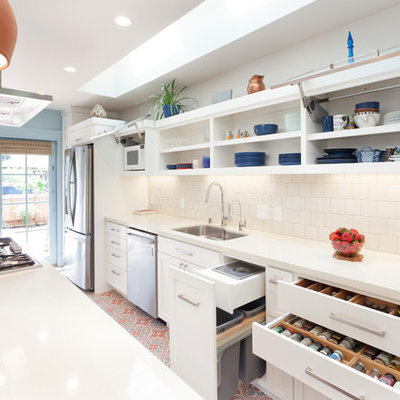 Example of a classic galley ceramic tile and multicolored floor kitchen design in San Francisco with an undermount sink, shaker cabinets, white cabinets, white backsplash, stainless steel appliances, an island, subway tile backsplash, white countertops and quartzite countertops