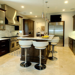 This is an example of a mid-sized modern u-shaped kitchen pantry in Tampa with dark wood cabinets, stainless steel appliances, porcelain floors and with island.