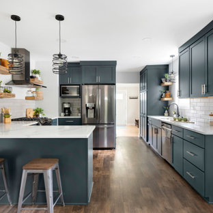 Photo of a mid-sized transitional u-shaped eat-in kitchen in Minneapolis with an undermount sink, shaker cabinets, blue cabinets, quartz benchtops, grey splashback, ceramic splashback, stainless steel appliances, vinyl floors, a peninsula, brown floor and white benchtop.