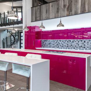 Inredning av ett modernt mycket stort linjärt kök och matrum, med en undermonterad diskho, släta luckor, bänkskiva i kvarts, svart stänkskydd, stänkskydd i glaskakel, integrerade vitvaror och klinkergolv i porslin