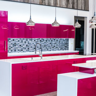 Inspiration for an expansive contemporary single-wall eat-in kitchen in New York with an undermount sink, flat-panel cabinets, quartz benchtops, black splashback, glass tile splashback, panelled appliances and porcelain floors.