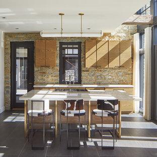 Inspiration pour une cuisine chalet avec un évier encastré, un placard à porte plane, des portes de placard en bois brun, une crédence multicolore, une crédence en carrelage de pierre, un îlot central, un sol gris et un plan de travail blanc.