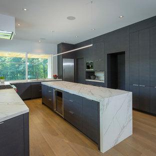 シンシナティの大きいコンテンポラリースタイルのおしゃれなキッチン (ドロップインシンク、フラットパネル扉のキャビネット、黒いキャビネット、オニキスカウンター、シルバーの調理設備の、淡色無垢フローリング、ベージュの床、マルチカラーのキッチンカウンター) の写真