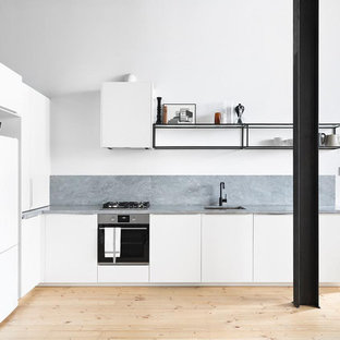 Inspiration for a modern l-shaped kitchen in Melbourne with an undermount sink, flat-panel cabinets, white cabinets, grey splashback, light hardwood floors, a peninsula, beige floor and grey benchtop.