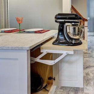 Modelo de cocina comedor en U, de estilo americano, grande, con fregadero sobremueble, armarios estilo shaker, puertas de armario blancas, encimera de esteatita, salpicadero verde, salpicadero de azulejos de piedra, electrodomésticos de acero inoxidable, suelo de baldosas de porcelana y una isla