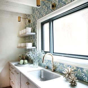 Modelo de cocina moderna con fregadero bajoencimera, armarios con paneles lisos, puertas de armario blancas, encimera de cuarcita, salpicadero azul, salpicadero de azulejos de cemento, electrodomésticos de acero inoxidable y suelo de ladrillo